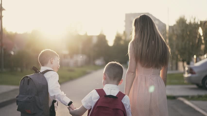 Tracking: Young mother goes with the children with school children, they tell her about successes, she smiles and praises them, raises her finger up.  | Shutterstock HD Video #1012835297