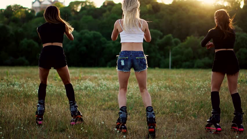 Group training kangoo. Three girls at sunset perform dynamic squats aimed at slimming and strengthening the muscles of the thighs #1012835816