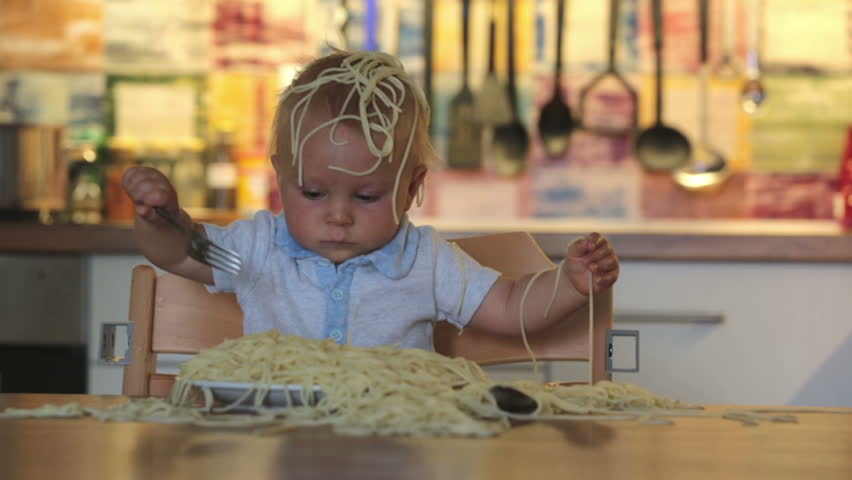 Little baby boy, toddler child, eating spaghetti for lunch and making a mess at home in kitchen | Shutterstock HD Video #1012838321
