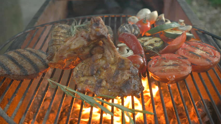 Assorted grilled meat with vegetables, in the foreground burger cutlet, steak on the bone, ribs, fire is breaking down from underneath the grill, in the background grilled vegetables, zucchini | Shutterstock HD Video #1012848500