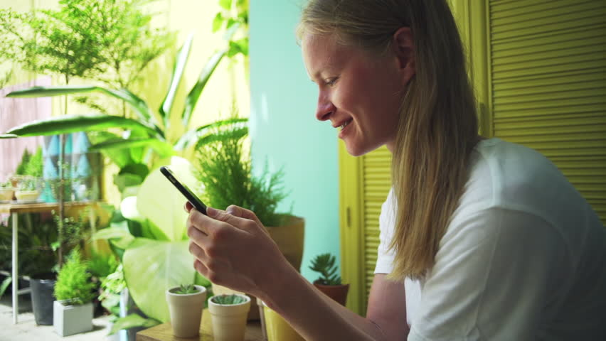 Happy girl use smartphone in bright interior background rapid slow motion | Shutterstock HD Video #1012853345