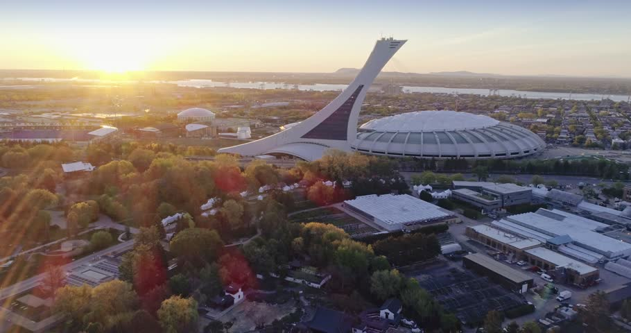 MONTREAL, QUEBEC, CANADA, 22 May 2018. AERIAL: Flying over the Montreal Olympic Stadium at sunrise. It is located at Olympic Park, uses in the 1976 Olympics, in the Hochelaga-Maisonneuve district