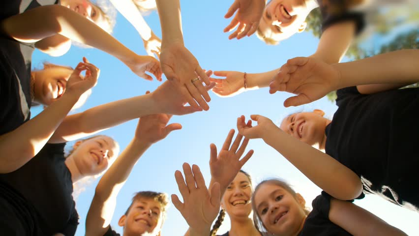 Group of school kids performs sports motivational greeting with hands on playground of yard football at sunny day   Shutterstock HD Video #1012886027