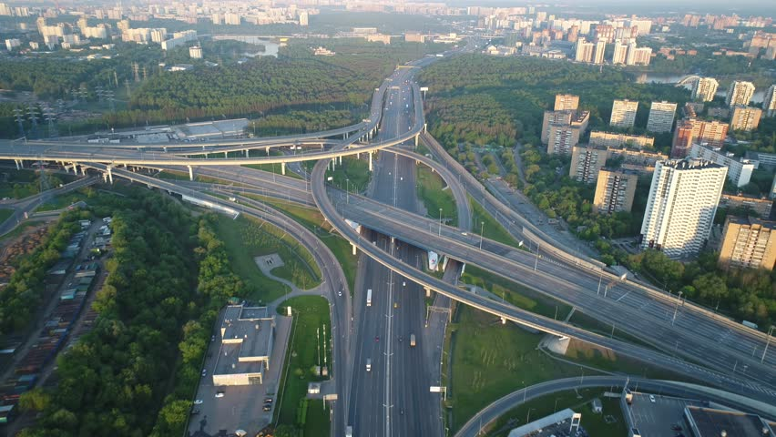 Aerial view. Flyght over a huge interchange of the Moscow ring road in the early morning at dawn from high altitude. Cars are moving on a multi-level road junction. Big city in background. | Shutterstock HD Video #1012887473