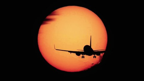 Silhouette of jumbo jet plane landing with big sun in the background, high contrast