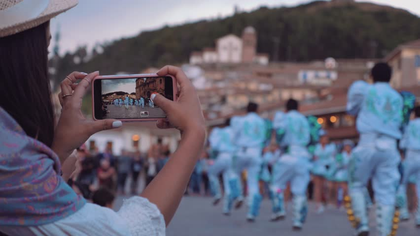 Beautiful Hispanic Woman shooting video with smartphone to folkloric dancers in Cusco, Peru Royalty-Free Stock Footage #1012902992