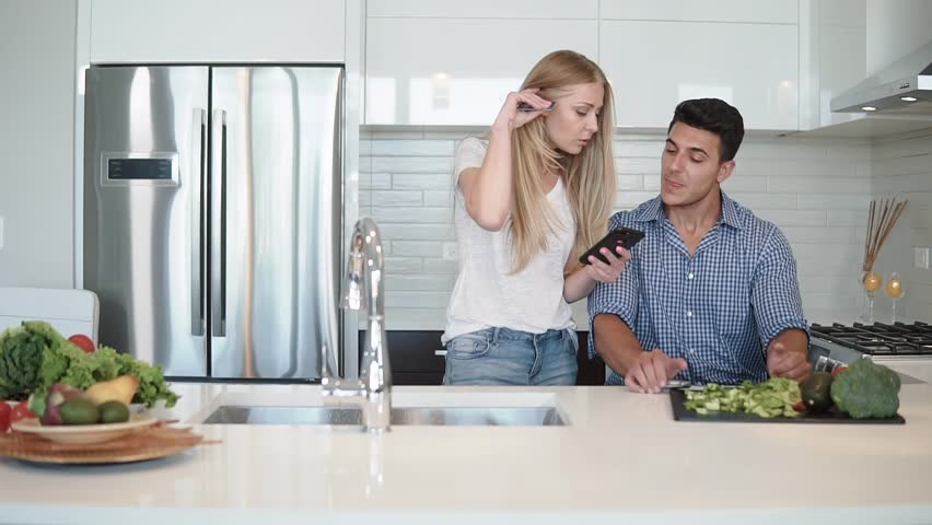 Beautiful young family in the kitchen with a telephone #1012909733