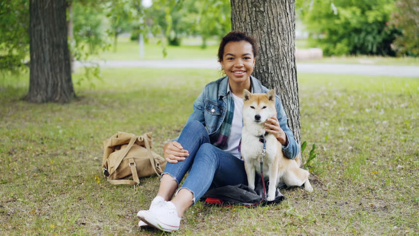 Portrait of African American girl loving dog owner sitting in park on grass with her beautiful pet, smiling and looking at camera. Loving animals and nature concept. | Shutterstock HD Video #1012911767