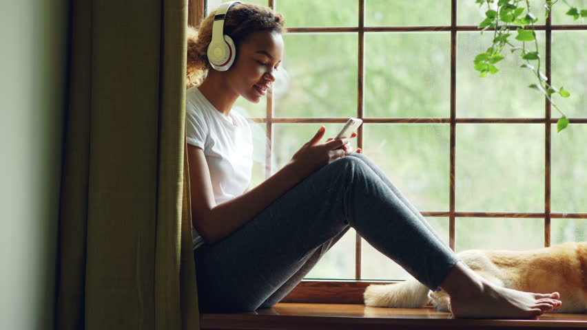Pretty African American girl is listening to music with headphones and using smartphone sitting on window sill with lovely well-bred dog lying near her. #1012911785