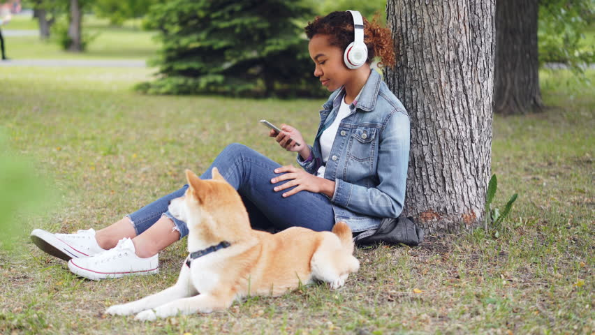Attractive African American woman is listening to music with headphones and using smartphone sitting on grass in park while her dog is lying nearby eating grass. | Shutterstock HD Video #1012911926