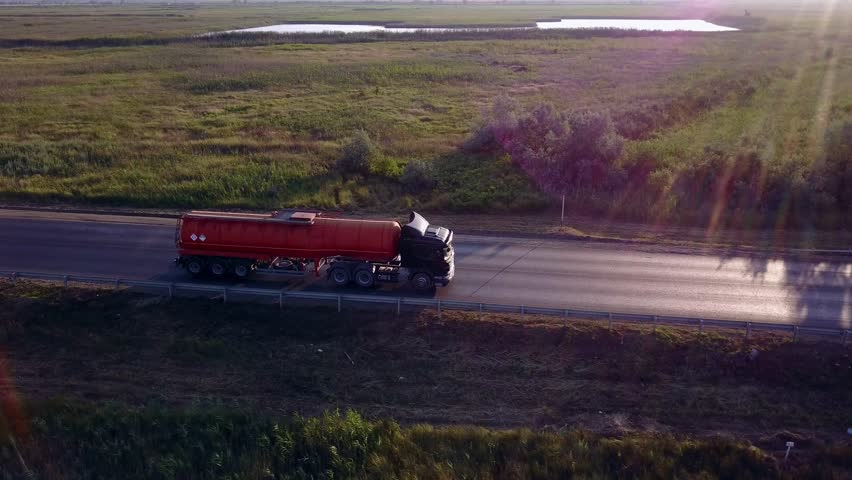 AERIAL: Gasoline tanker, Oil trailer, truck on highway. Very fast driving