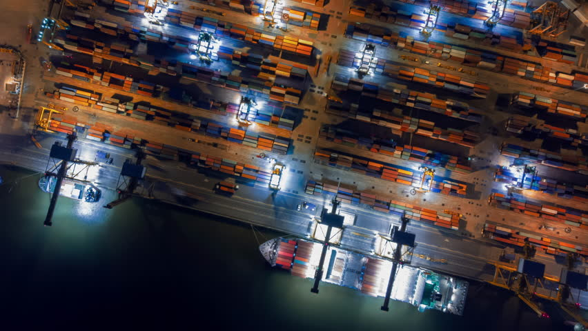 Aerial view drone time-lapse or hyper-lapse over industrial port in Bangkok Thailand with many container vessel ship and big crane working at night.