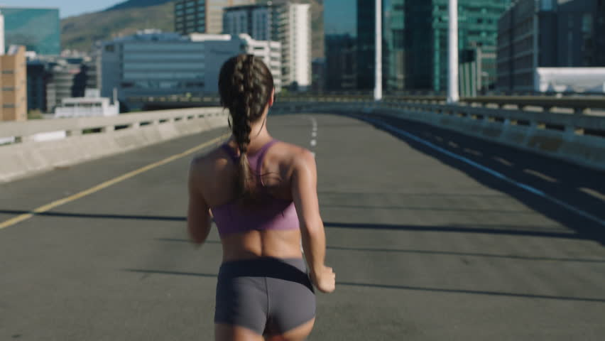 Fit young woman athlete running in city jogging exercising enjoying healthy fitness lifestyle female runner on sunny urban road rear view | Shutterstock HD Video #1012928252