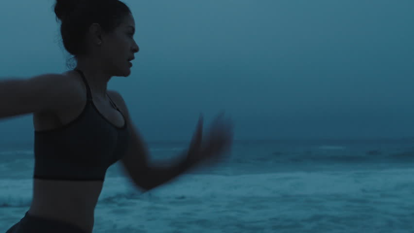 strong young woman running on stormy beach sprinting fast exercising cardio workout training focused female athlete runner in cloudy seaside background tracking close up