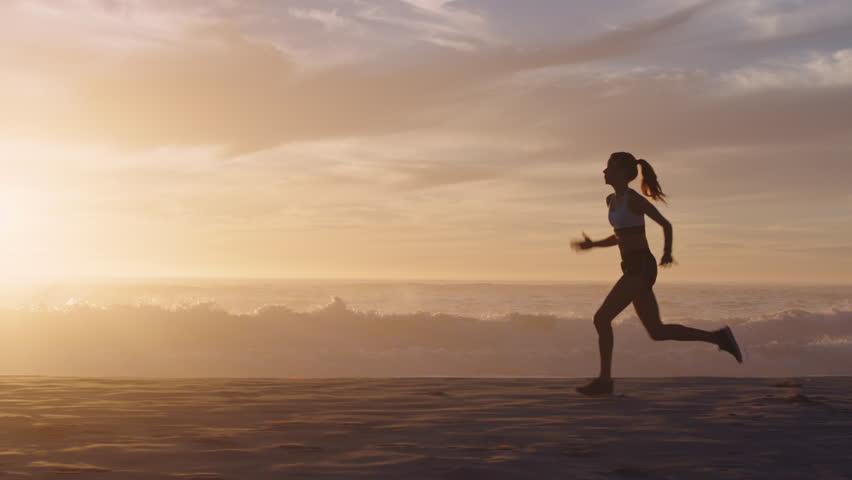 Woman silhouette running on beach waves splashing female runner exercising sprinting intense workout on beautiful ocean seaside at sunset background | Shutterstock HD Video #1012930220