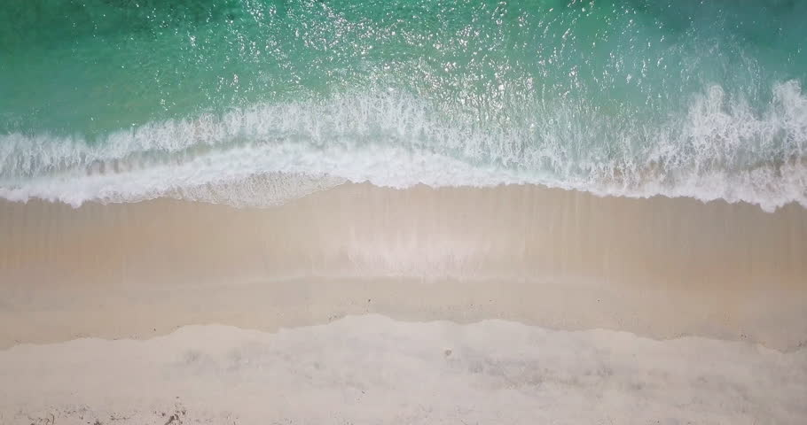 Top camera view over white sand beach and little waves of blue sea or ocean running on the shore. Summer beach background. Sand and sea. Aerial drone slow motion footage Uhd 4K. | Shutterstock HD Video #1012934000