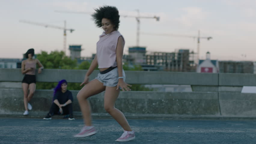 dancing woman attractive young mixed race dancer performing urban style street dance in city practicing freestyle moves friends watching enjoying hang out at sunset #1012940075