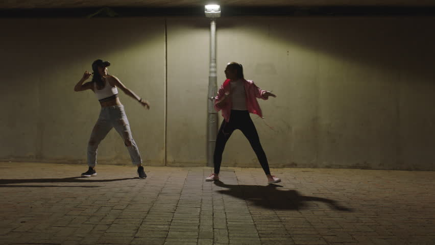 dancing woman young hip hop dancer girls under street light practicing contemporary freestyle dance moves practicing in city at night #1012941266
