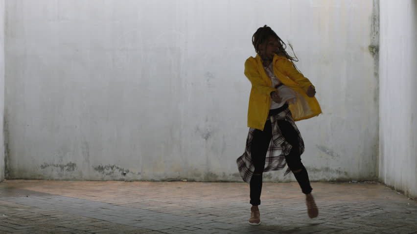 Close up young happy street dancer woman dancing performing freestyle hip hop moves enjoying modern dance expression practicing in grungy warehouse wearing yellow jacket