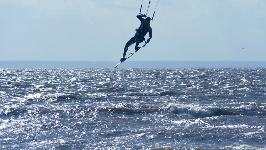 SLOW MOTION: Kiteboarder rides on the board on the waves. Summer sunny evening.   Shutterstock HD Video #1012973021