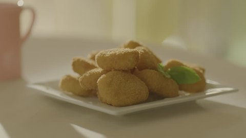 The child's hand takes an appetizing nuggets from the plate. Very beautiful studio shot. Slow motion. Camera Arri Alexa.