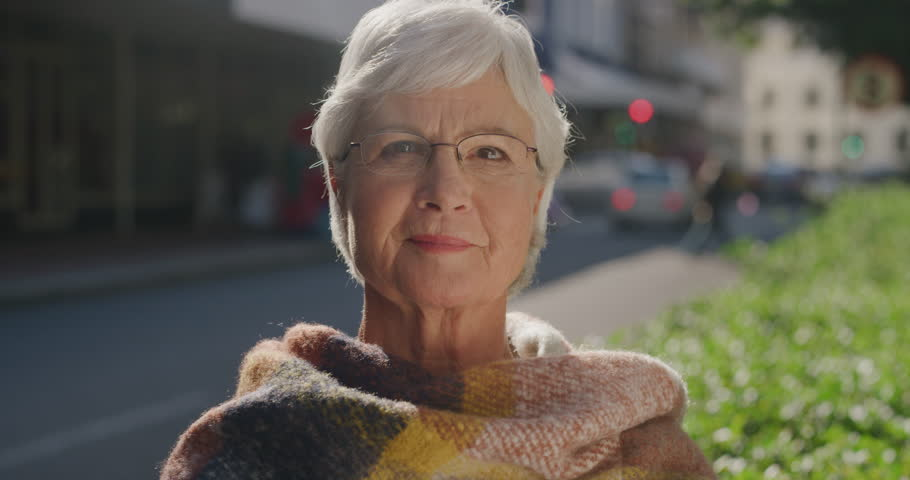 Portrait of happy old woman smiling cheerful enjoying successful retirement lifestyle on sunny urban day in city street wearing scarf confident retired caucasian female | Shutterstock HD Video #1012992395