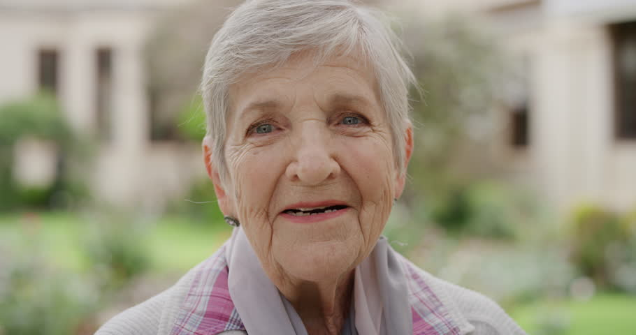 close up portrait of elderly caucasian woman smiling cheerful looking at camera enjoying sunny day in park happy retired #1012995785