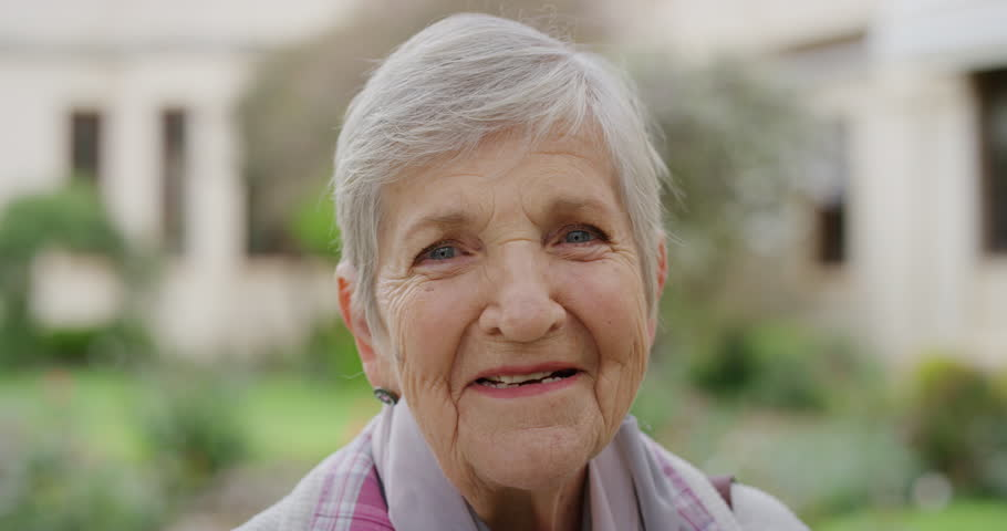 close up portrait of elderly caucasian woman smiling cheerful at camera enjoying sunny day in park happy retired #1012995791