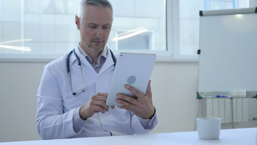 Doctor Using Tablet for Browsing Internet   Shutterstock HD Video #1013000540