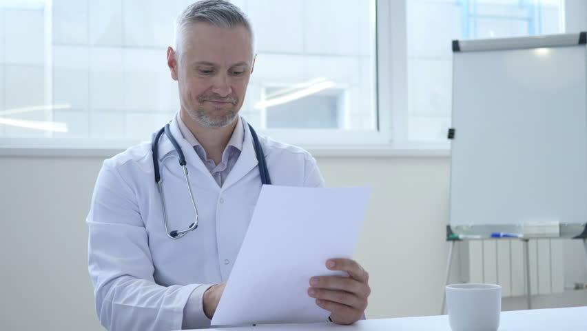Happy Doctor Reading Medical Report of patient   Shutterstock HD Video #1013000555