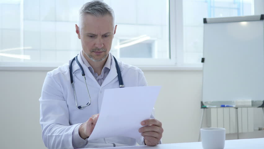 Doctor Reading Medical Papers in Clinic | Shutterstock HD Video #1013000567