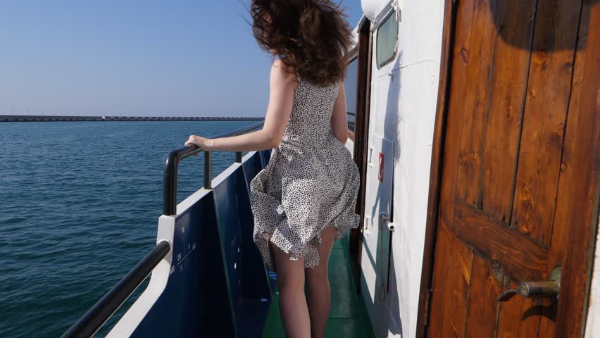 Happy young adult woman with long wavy hair and light flying dress run forward at ship deck, slow motion shot. Girl excited by nice sunny weather and good trip on old boat | Shutterstock HD Video #1013008325