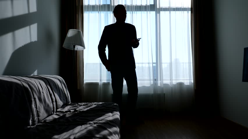 Busy guy wearing casual suit talk on phone and check other smartphone, walk against living room window. Silhouetted shot, bright sun light shine from outside | Shutterstock HD Video #1013008343