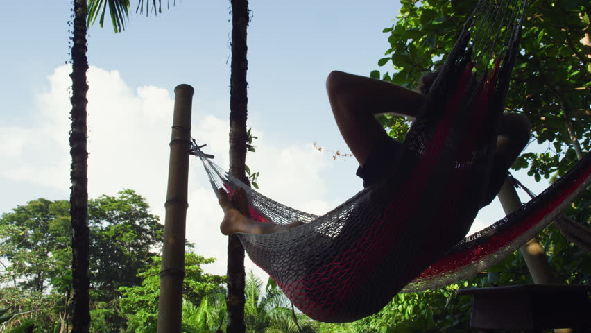 A beautiful cinematic shot of a young man relaxing in hammocks at an ecolodge resort with views of palm trees and other rainforest jungle vegetation in Costa Rica. Shot in 5K.