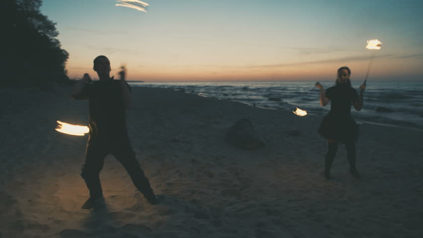 The guy and the girl is showing a fire show on the beach. 4K