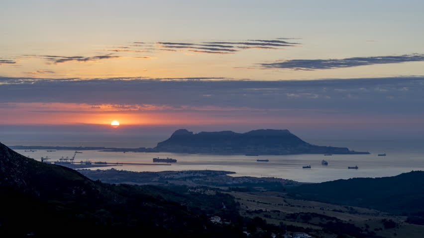 Algeciras, Andalusia, Spain. Sunrise Time lapse of the panoramic view of Gibraltar, with clouds and the great ships crossing the Strait of Gibraltar. | Shutterstock HD Video #1013016752