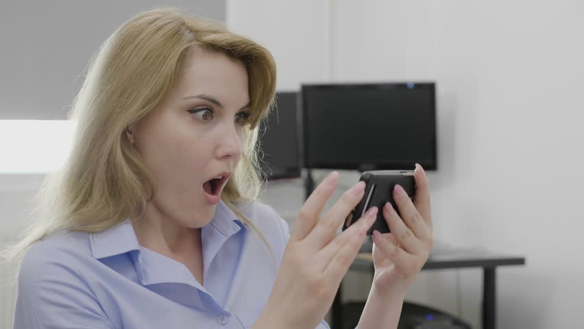 Shocked young businesswoman receiving surprising breaking news on her smartphone at work