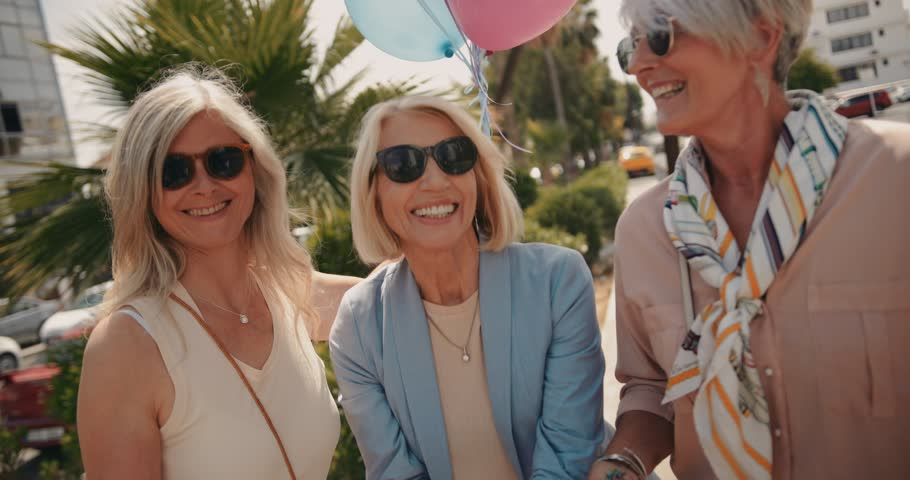 Happy senior female friends having fun in the city and celebrating with balloons and confetti #1013028470