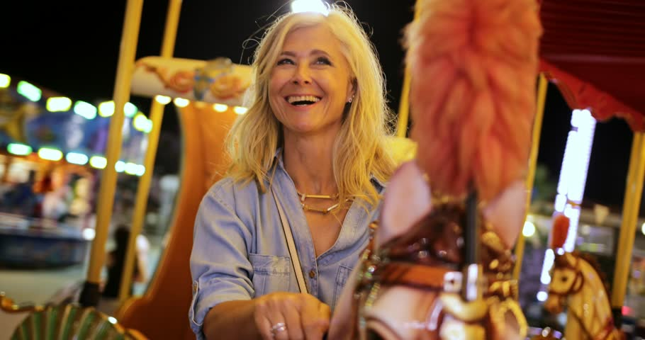 Happy fashionable senior woman on summer vacations having fun on funfair merry-go-round ride at night Royalty-Free Stock Footage #1013028500