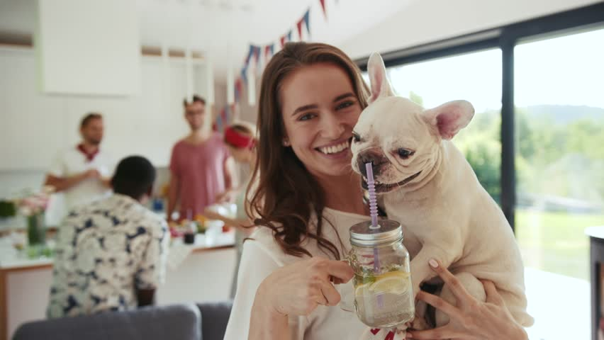 Pretty young woman holds her cute french bulldog puppy on her hands, and drinks homemade fresh summer drink out of the mason jar with straw, dog wants to taste some, she is happily smiling. Royalty-Free Stock Footage #1013030708