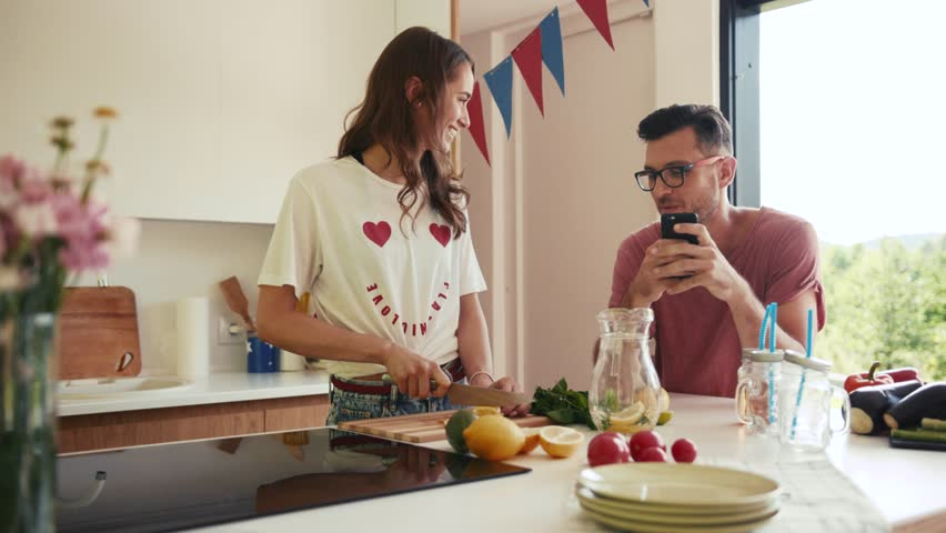 Attractive young man and woman having a pleasant conversation on the kitchen, he shows her something on his phone, she cuts lemon and cutely smiles to him. Romantic atmosphere, flirting.