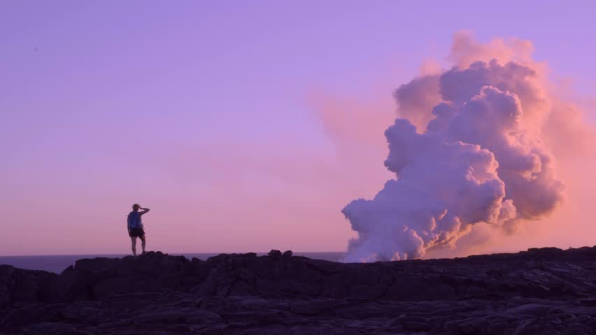 Woman Standing by Erupting Kilauea Volcano at Sunset in Hawaii