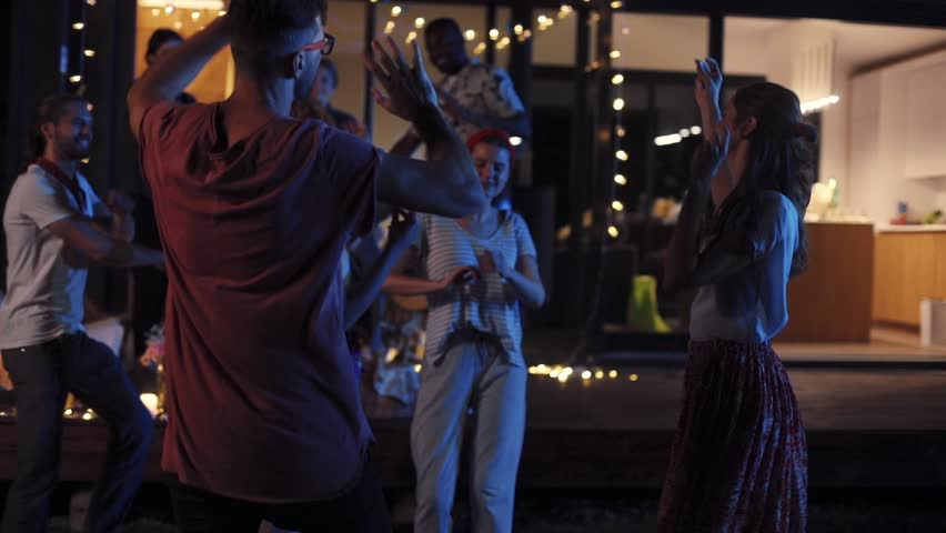 Beautiful friends dancing near modern house in evening. Young people having fun together, celebrating in the open air. Party. Summertime. Outside. | Shutterstock HD Video #1013038451