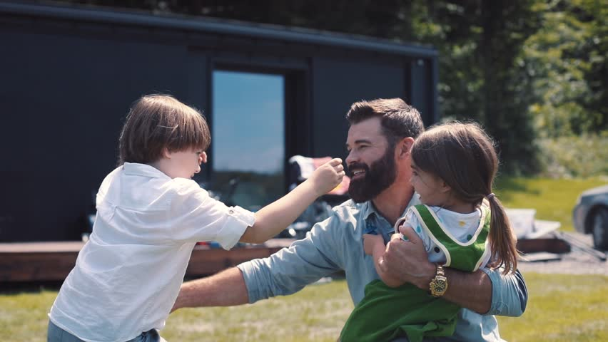 Happy Caucasian children running to meet dad. Little boy and girl hugging daddy. Father coming home. Country house. Daytime. Outside. Best moments. | Shutterstock HD Video #1013038997