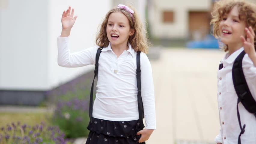 A pair of curly schoolchildren, a boy and a girl, say goodbye, waving their hands, looking at the camera, unfolding and leaving. Goodbye school, back to school | Shutterstock HD Video #1013043170