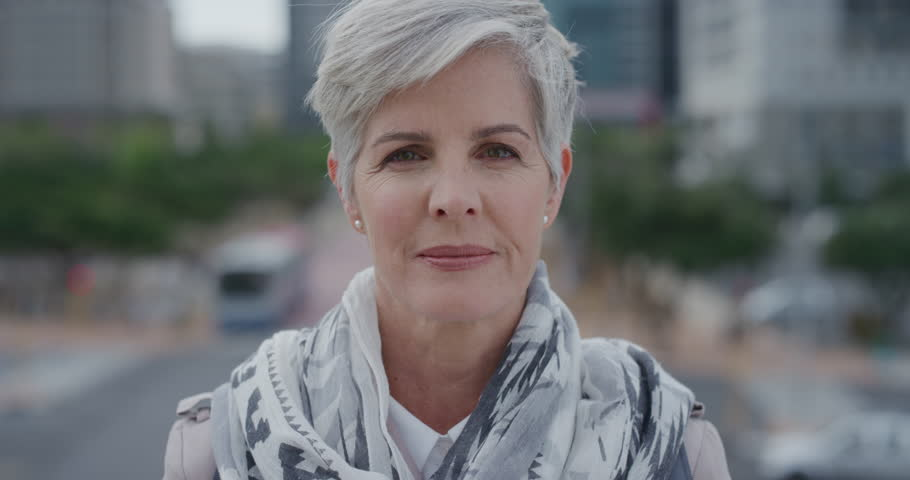 portrait beautiful middle aged caucasian woman smiling enjoying successful urban lifestyle in city slow motion #1013050493