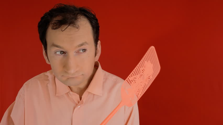 A funny ugly man trying to squash a fly with a swatter, but ending up hitting himself on the head. Red background.