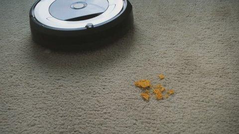 Robot vacuum cleaner cleaning crumbs off floor