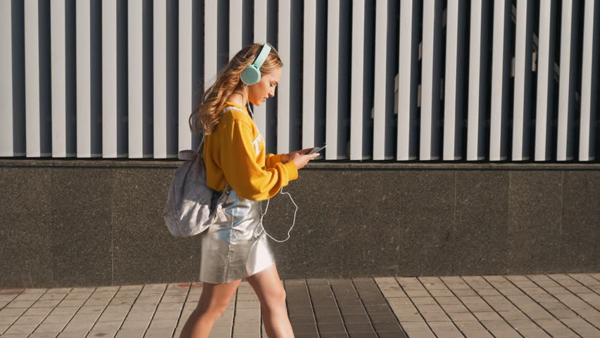 Portrait of young cute attractive young girl in urban background listening to music with headphones. Woman wearing yellow blouse and silver skirt. | Shutterstock HD Video #1013067575