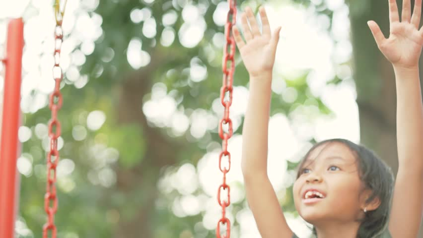 Asian little girl playing on the swing at the park in summer time. Shot in 4k resolution | Shutterstock HD Video #1013070839
